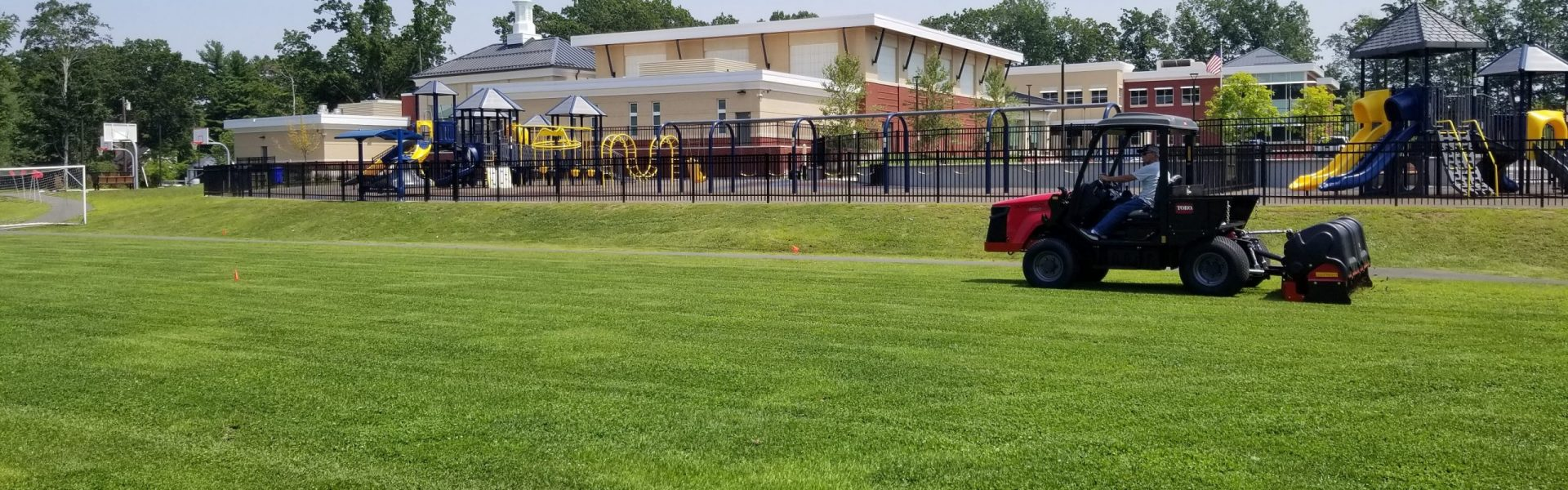athletic fields on school grounds with tractor