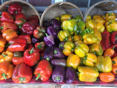 red, purple and yellow peppers in baskets at a farm stand